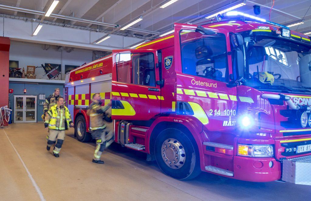 Några brandmän springer mot en röd brandbil i en vagnhall. Brandmännen är suddiga av farten.