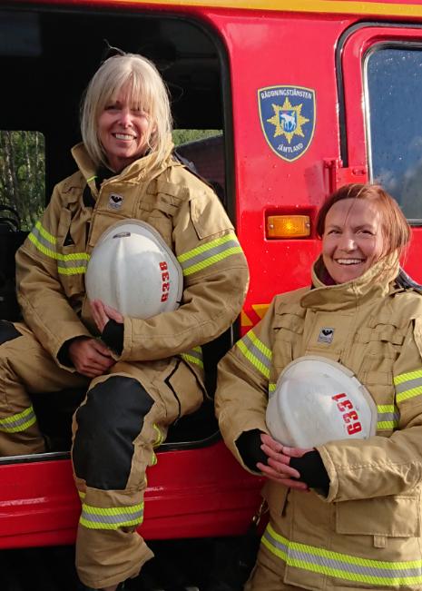 Två kvinnliga brandmän bredvid en av Jämtlands brandbilar.