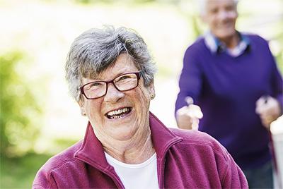 En äldre dam och herre är ute och går stavgång. De ler stort i det härliga sommarvädret.