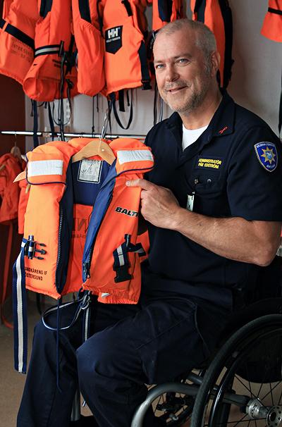 En glad man håller upp en liten orange flytväst. Han sitter i en rullstol och har flera flytvästar bakom sig på väggen
