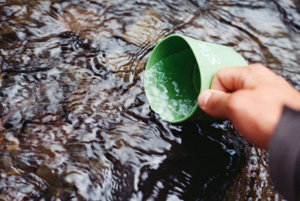 En ljusgrön kåsa sänks ned i grunt vatten.
