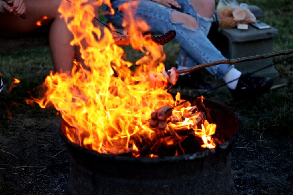 Eldplats där två personer grillar ute i naturen