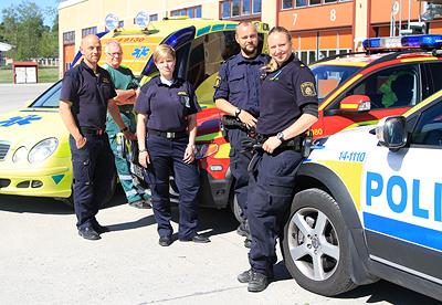 Gruppbild med bilar och personal från ambulans, räddningstjänst och polis.  Tre herrar och två damer, samt tre bilar.