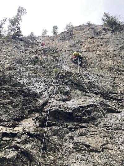 Person som klättrar i berg med skyddssele och rep