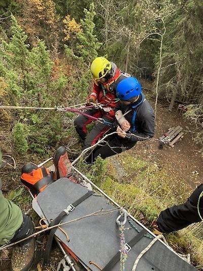 2 bergsklättrare med rep och bår som hjälper person