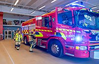 Några brandmän i beiga larmställ springer till en röd brandbil i vagnhallen i Östersund.