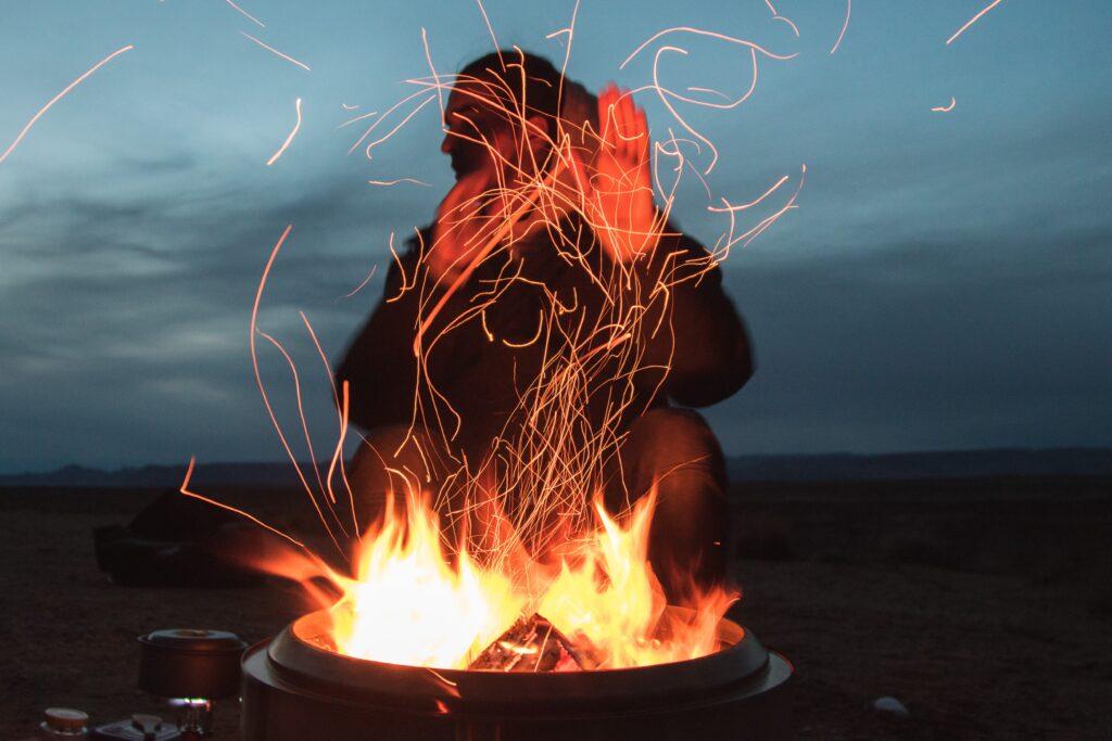 En ensam man sitter bakom en liten brasa, han håller upp sina händer framför elden och tittar åt vänster i bilden. Det är mörkt omkring.