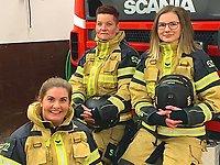 Tre kvinnliga brandmän framför en brandbil