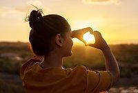 En kvinna står med ryggen mot oss framför ett öppet landskap. Det är solnedgång och hon formar ett hjärta med händerna runt solen.