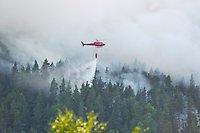 En röd helikopter som släcker en skogsbrand från luften