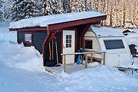 Ett spiketält i anslutning till en vid husvagn i ett snöigt landskap.