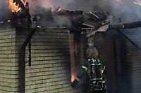 En brandman står och tittar in vid ett fönster i ett tegelhus i gult. Det brinner i rummet och vid takfoten - takplåt hänger deformerat över brandmannen...
