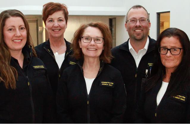Fem glada medarbetare från kansliet i gruppbild. Det är fyra kvinnor och en man. De har på sig mörkblåa uniformer.