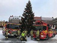 Styrkan på 6 man står framför sina två röda brandbilar framför den stora julgranen på Stortorget i Östersund.