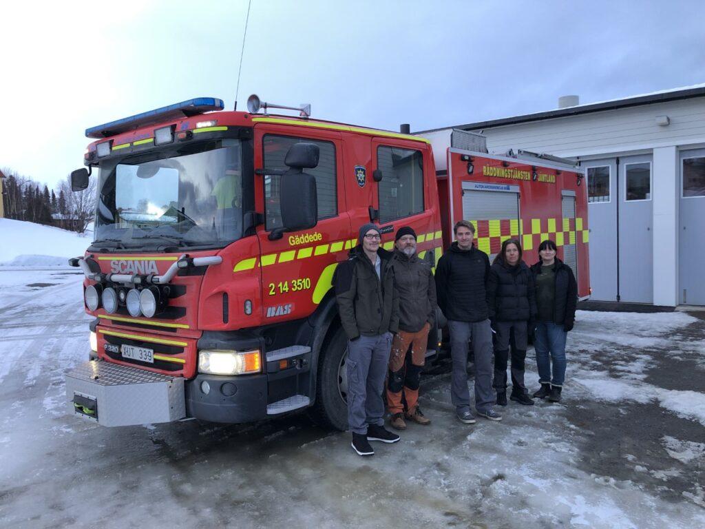 En röd brandbil med fem glada brandmän i civila kläder.